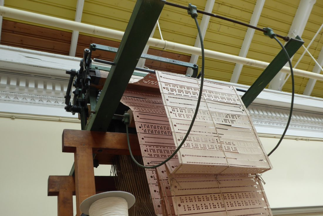 The punch cards used by the Jacquard loom are pictured. Long strips of card are sewn together, each card has a sequence of holes in it. The holes in the card correspond to a line of pattern in the woven fabric.